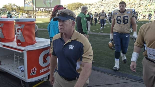 Winnipeg Blue Bombers head coach Tim Burke leaves the field after the team lost 0-52 to the Saskatchewan Roughriders on Sunday in Regina.