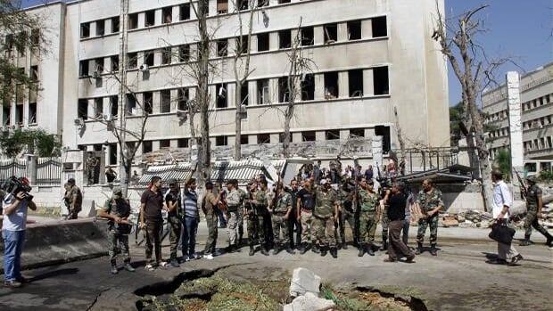 Syrian soldiers stand at the site of twin bombings near the headquarters of the armed forces general staff in Damascus on Wednesday.