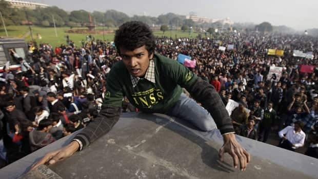 A man climbs on the roof of a police bus in New Delhi on Saturday, part of a protest against the gang rape of a 23-year-old student on a bus.
