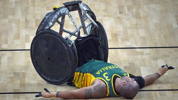 An Australian wheelchair rugby player is seen post-fall during a match against Canada in April. Some paralympic athletes have admitted to inducing a dangerous condition, Autonomic Dysreflexia, to boost their performance in this fast-paced sport.