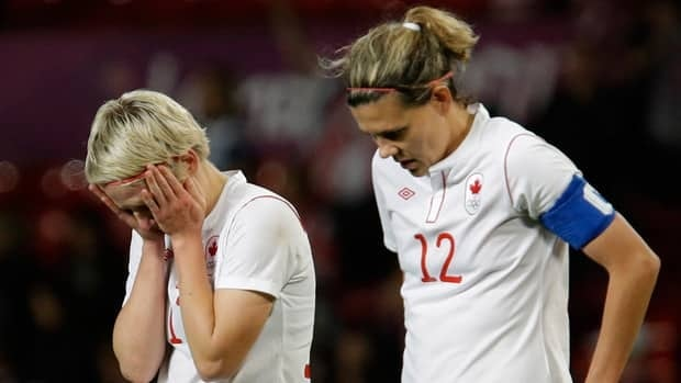 Canada's captain Christine Sinclair, right, and midfielder Sophie Schmidt walk off the pitch in total shock after losing a heartbreaking semifinal match to the Americans on Monday.
