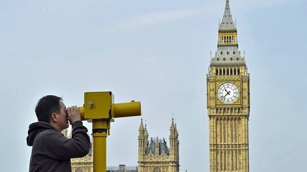 A man looks through a telescope opposite Big Ben and the Houses of Parliament, in central London. The Olympics weren't the tourism boom for London that some people had expected.