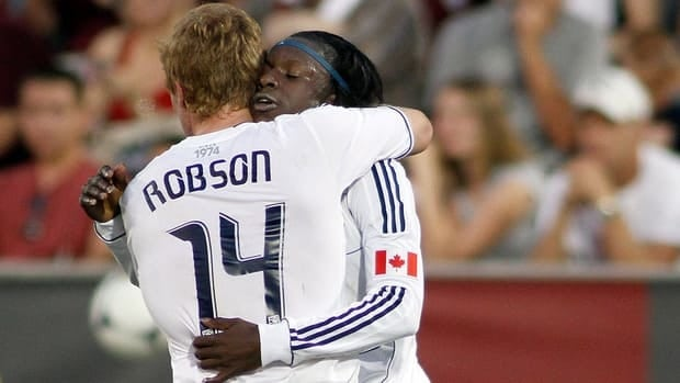 Vancouver's Darren Mattocks, back, is congratulated by teammate Barry Robson (14) after scoring against the Colorado Rapids Wednesday in Commerce City, Colo.