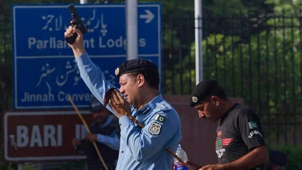 A police officer fires into the air during clashes that erupted as demonstrators tried to approach the U.S. Embassy in Islamabad on Friday.