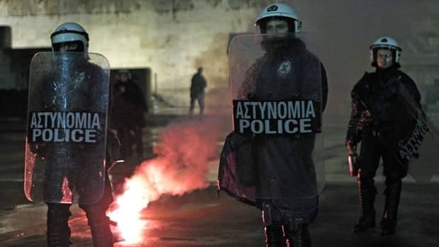 Riot policemen guard the Greek parliament as a flare thrown by protesters burns during a protest in Athens Wednesday. Police said some 6,500 people took part in two separate peaceful protests outside Parliament, called by the country's two main unions and a Communist union.