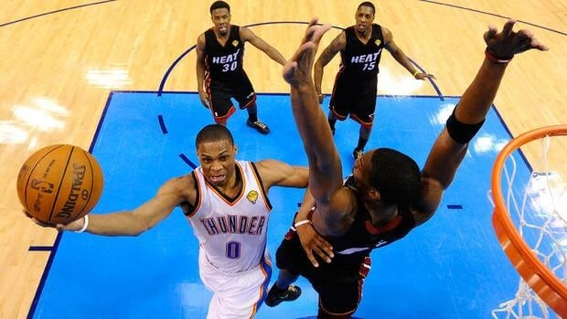 Oaklahoma City Thunder's Russell Westbrook, left, drives past Miami Heat's Chris Bosh, right,  during Game 2 of the NBA Finals.