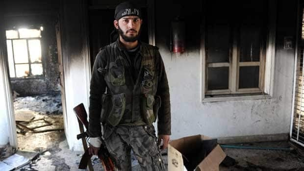 A Syrian opposition fighter is pictured in a destroyed house after hard clashes with Syrian regime forces in Ras al-Ain on Nov. 10, 2012.
