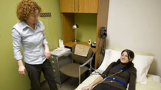 Psychology student Molly Atwood, right, lies in bed while being monitored by Ryerson University's Dr. Colleen Carney, who studied how poorer sleepers were more startled in the dark than better sleepers.