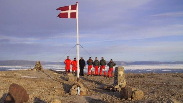 The crew of the Danish warship Vedderen perform a flag raising ceremony on uninhabitated Hans Island in August 2002. Canadian Forces performed a similar ceremony in 2005. The island is midway between Ellesmere Island and Greenland, and both Canada and Denmark claim sovereignty over it.