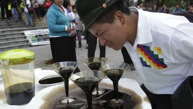 "An indigenous protester in Ecuador looks at ""oil martinis"" in Quito, during a protest against oil companies. The Ontario Superior Court in Toronto will be the latest venue in a bitter 19-year legal fight between Chevron Corp. and dozens of Ecuadorian Amazon villagers."