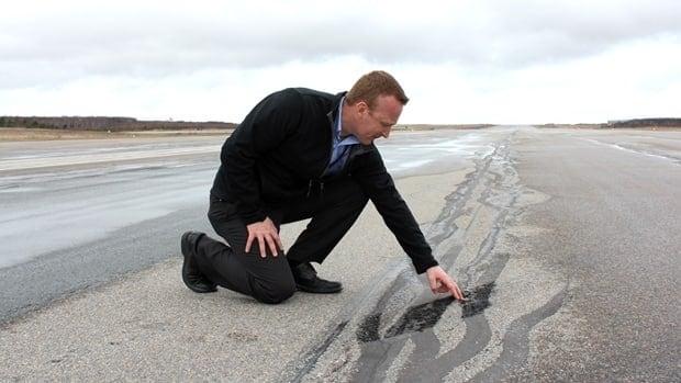 Stephen Burbridge, manger of infrastructure at Gander International Airport, runs his fingers along cracks on a runway.