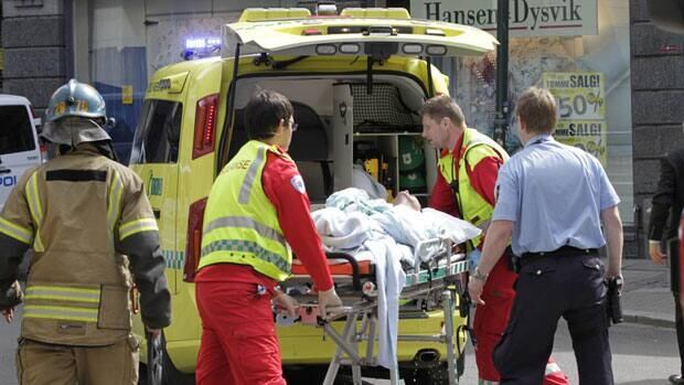 A man who set fire to himself outside the courthouse in Oslo Tuesday, where the trial of Anders Behring Breivik is taking place, is taken into an ambulance.