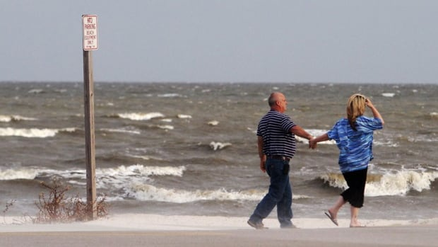 A couple walk along the beach on Thursday in Gulfport, Miss. Preparations are underway along the Mississippi Gulf Coast as tropical storm Karen moves through the Gulf of Mexico.