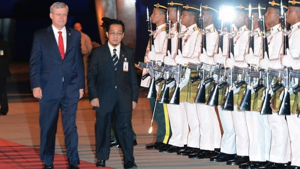 Prime Minister Stephen Harper is escorted by an official upon his arrival in Kuala Lumpur late Friday, to take part in a bilateral visit. Harper will travel on to the APEC leaders' meeting in Bali, Indonesia.