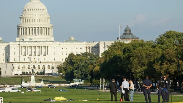 Law enforcement officials investigate the scene where a man set himself on fire in front of the U.S. Capitol building on the U.S. National Mall in Washington. The man was rushed to a local hospital by helicopter after using fuel to set himself ablaze.