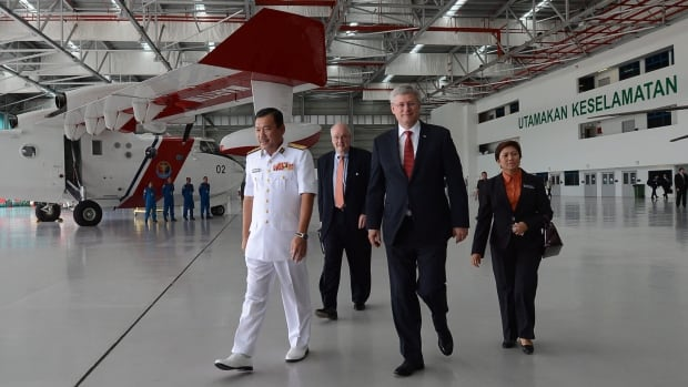 Prime Minister Stephen Harper and Ward Elcock, back left, Office of the Special Adviser on Human Smuggling and Illegal Migration in the Privy Council Office, walks with Admiral Datuk Mohd Amdan Kurish, left, on a tour of the Malaysian Maritime Enforcement Authority Air Station in Kuala Lumpur on Saturday.