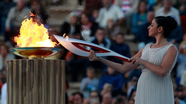 Actress Ino Menegaki, playing the role of high priestess, lights the torch with the Olympic Flame during a handover ceremony in Athens' Panathinaiko Stadium, on Saturday.