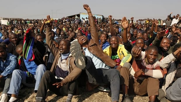 Striking miners hold up their hands as they are addressed by former African National Congress Youth League president Julius Malema outside the Lonmin platinum mine in South Africa on Aug. 18, 2012.