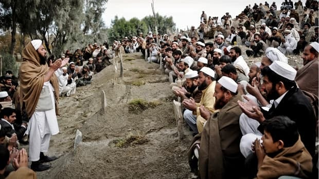 Afghans pray for the young girls killed from a mine explosion in Chaparhar, Nangarhar province east of Kabul, Afghanistan, on Monday.