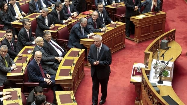 Newly appointed caretaker Prime Minister Panagiotis Pikrammenos walks in front of parliamentarians before a swearing-in ceremony at the Presidential palace in Athens May 17, 2012.