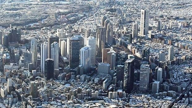 High-rise buildings IN Tokyo's Shinjuku district are covered with overnight snow in Tokyo.