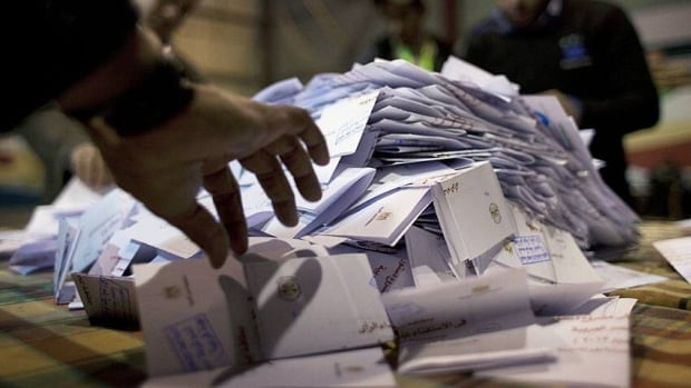 Egyptian election workers count ballots at the end of the second round of a referendum on a disputed Islamist-backed constitution at a polling station in Giza, Egypt, on Saturday. Final results of the vote are due to be released Monday, but may be delayed by an investigation into allegations of fraud.