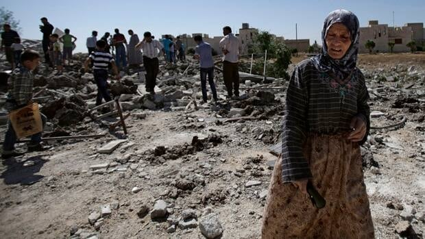 A Syrian woman stands amid the rubble of a house destroyed by Syrian artillery early Monday in Azaz, on the outskirts of Aleppo. Muhammed Muheisen/Associated Press