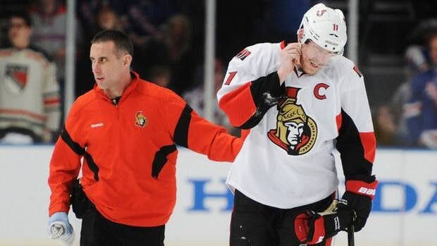 Ottawa Senators Daniel Alfredsson is tended to by a trainer during a break in play against the New York Rangers during the second period of Game 2 in New York on Saturday.