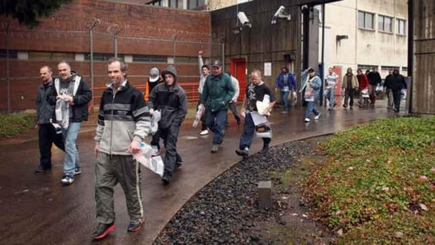 Thirty-one inmates leave the Lane County Jail in Eugene, Ore., Thursday as part of a budget measure in this photo from the Eugene Register-Guard. One of the men was accused of bank robbery less than an hour later.