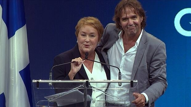 Pauline Marois and Yves Desgagnés on stage at a Montreal concert hall after the PQ leader was permitted to return to the podium following the shooting.