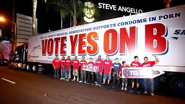Supporters of the condoms in porn measure, led by the AIDS Healthcare Foundation, hand out voter information and free condoms on L.A's famed Sunset Strip.