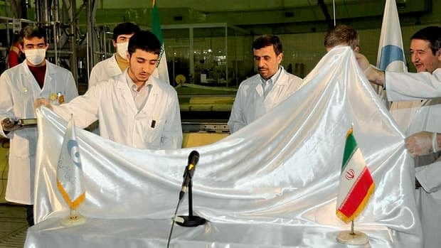 What's under the plastic? Iran's President Mahmoud Ahmadinejad, fourth left, attends an unveiling of new nuclear projects in Tehran Feb. 15, 2012.