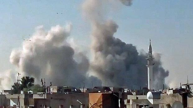 Smoke rises from buildings from heavy shelling in Homs, Syria, on Thursday, Dec. 27, 2012.