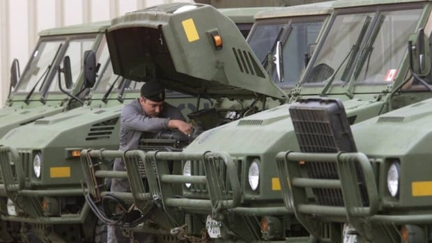 A vehicle technician makes some adjustments to a truck at Canadian Forces Base Edmonton. The federal government has delayed the purchase of new military vehicles.