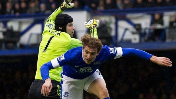 Everton's Nikica Jelavic, right, takes to the air with Chelsea goalkeeper Petr Cech during their English Premier League soccer match at Goodison Park Stadium on Sunday. Chelsea won the game to stay in the battle for first.