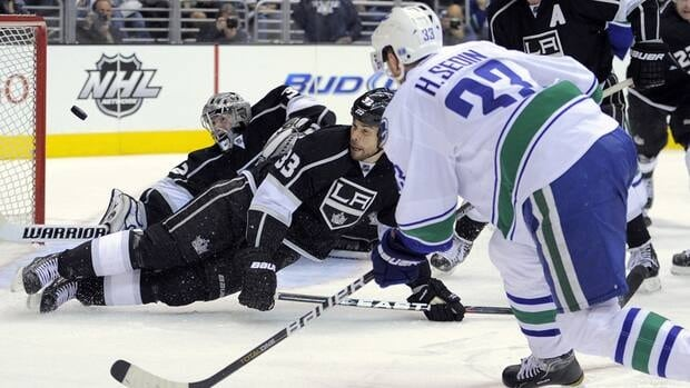 Vancouver Canucks centre Henrik Sedin, right, scores a goal on Los Angeles Kings goalie Jonathan Quick, left, as defenceman Willie Mitchell tries to get in the way on Wednesday night.