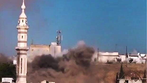 In this image made from amateur video released by the Ugarit News and accessed Monday, black smoke leaps the air from shelling near a mosque in Talbiseh, the central province of Homs, Syria.