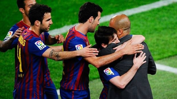 Lionel Messi of FC Barcelona hugs head coach Josep Guardiola after scoring his team's third goal during the match against Espanyol at Camp Nou on May 5, 2012 in Barcelona, Spain.