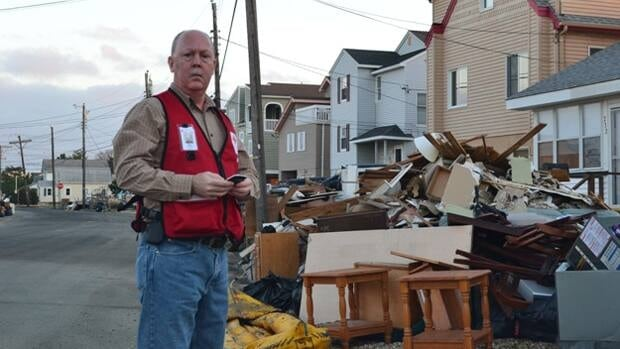 Volunteer Dan Bedell stands beside some of the piles of furniture, appliances and other belongings tossed from homes due to mold, mildew and other contamination concerns on Thanksgiving Day in Ship Bottom, N.J.