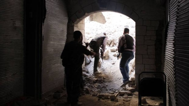 Members of the Free Syrian Army check for snipers in the old part of Aleppo on Tuesday.
