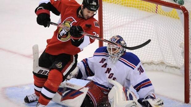 Ottawa Senators' Zenon Konopka keeps his eye on the puck as he attempts to score on New York Rangers' Henrik Lundqvist.