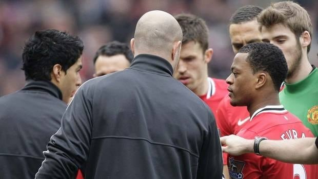 Manchester United's Patrice Evra, right, attempts to shake hands with Liverpool's Luis Suarez during their English Premier League soccer match at Old Trafford Stadium on Saturday. Suarez refused, setting off a boiling controversy.