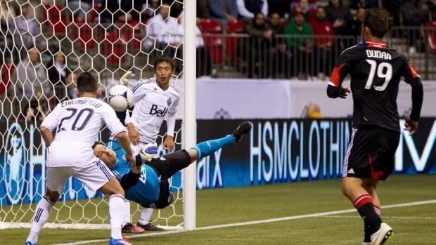 Vancouver Whitecaps' goalkeeper Joe Cannon, second left, stops D.C. United's Emiliano Dudar's, right, shot as Davide Chiumiento, left, and Young-Pyo Lee defend during the second half in Vancouver on Saturday.