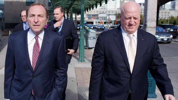 NHL Commissioner Gary Bettman, left, arrives with Bill Daly for collective bargaining talks in Toronto on Tuesday.