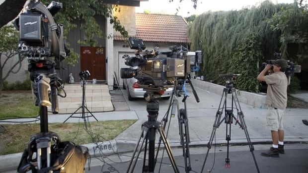 A cameraman keeps watch near media cameras outside the home of Nakoula Basseley Nakoula, who has been linked by U.S. federal authorities to the production of the anti-Muslim video, Innocence of Muslims, in Cerritos, Calif.