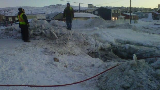 Workers stand near a burst water main in Iqaluit. The broken pipe unleashed a flood of water that drained much of the city's reservoir.