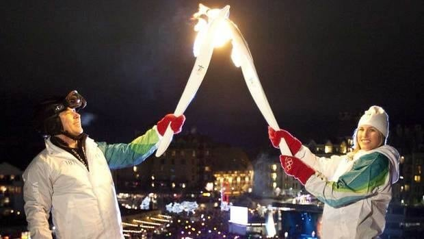 Steve Podborski, left, passed the Olympic flame to ski cross athlete Julia Murray prior to the 2010 Vancouver Games.
