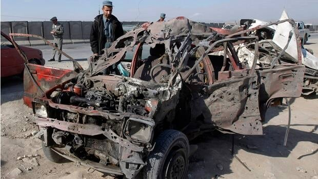 An Afghan policeman inspects a wreckage of a car driven by a suicide bomber in Jalalabad on Monday.