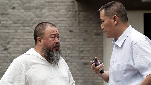 China is lifting some restrictions on dissident artist Ai Weiwei, seen at left talking with his lawyer at his Beijing home on Wednesday. However, he is still not permitted to leave the country.