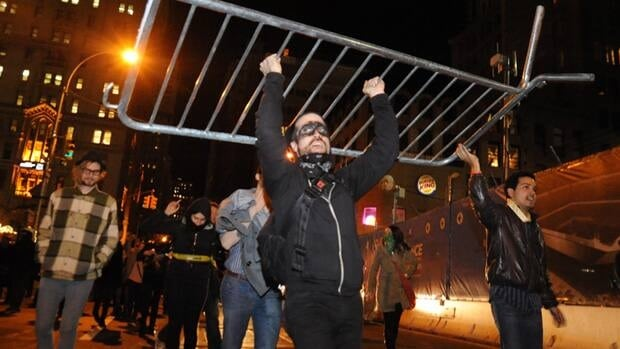 Occupy Wall Street protesters carry a barricade they removed from Zuccotti Park in New York on Saturday. The demonstrators took police barricades, piled them up and celebrated on top of them.